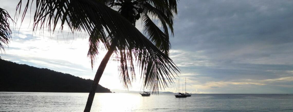 Zonsondergang boven de zee met palmboom en boten