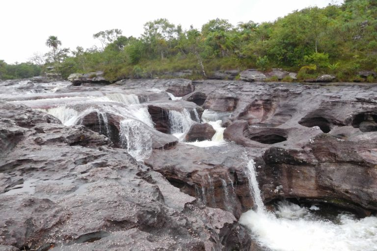 Waterfall, rocks with holes, trees, clouds