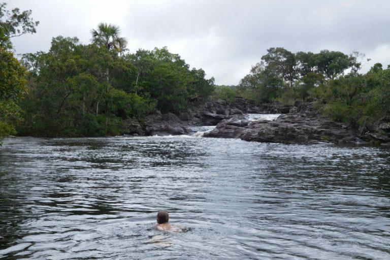 Dark water, Lies swimming back towards camera, trees, rocks, clouds