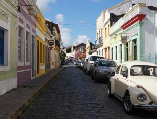 Kleurrijke straat in Olinda met eend en motor