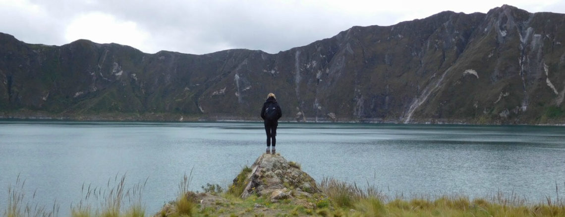 Lies op steen uitkijkend over het Quilotoa meer