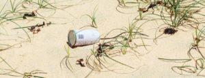Blikje zwerfafval in het zand