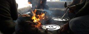 Mannen koken vegatrische maaltijd op bergtop